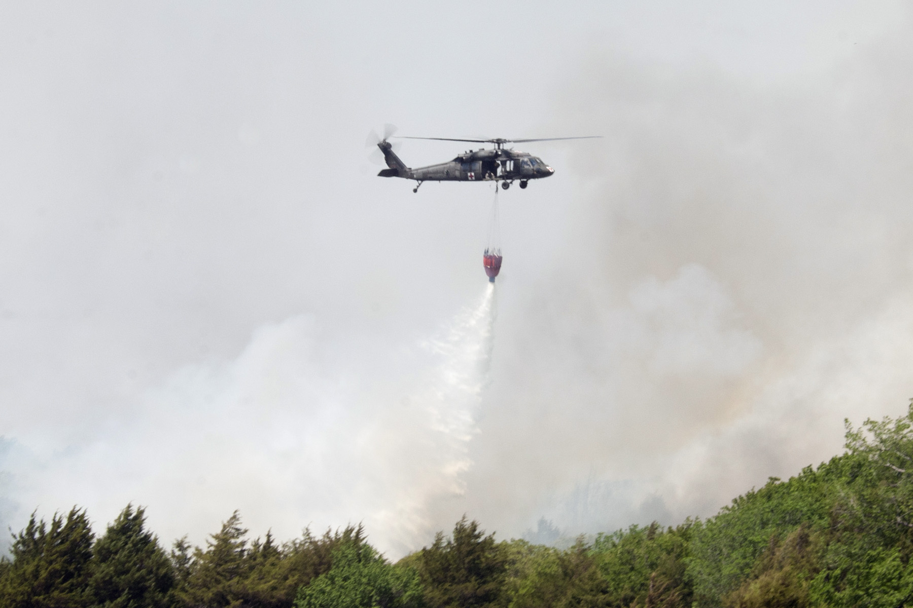 """A UH-60 """"Blackhawk"""" helicopter from the Oklahoma Army National Guard assists local fire fighters near Guthrie, Oklahoma, as they attempt to contain wildfires that claimed more the 6,000 acres of land and numerous homes in less than 24 hours."""