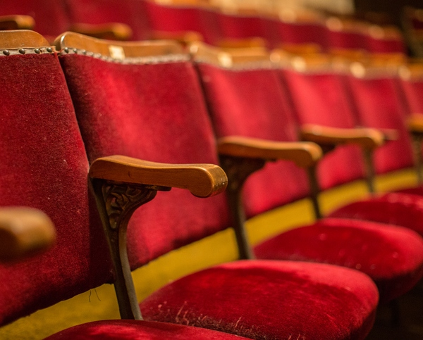 Old fashion cinema theatre seats with wooden arms flip-up seats
