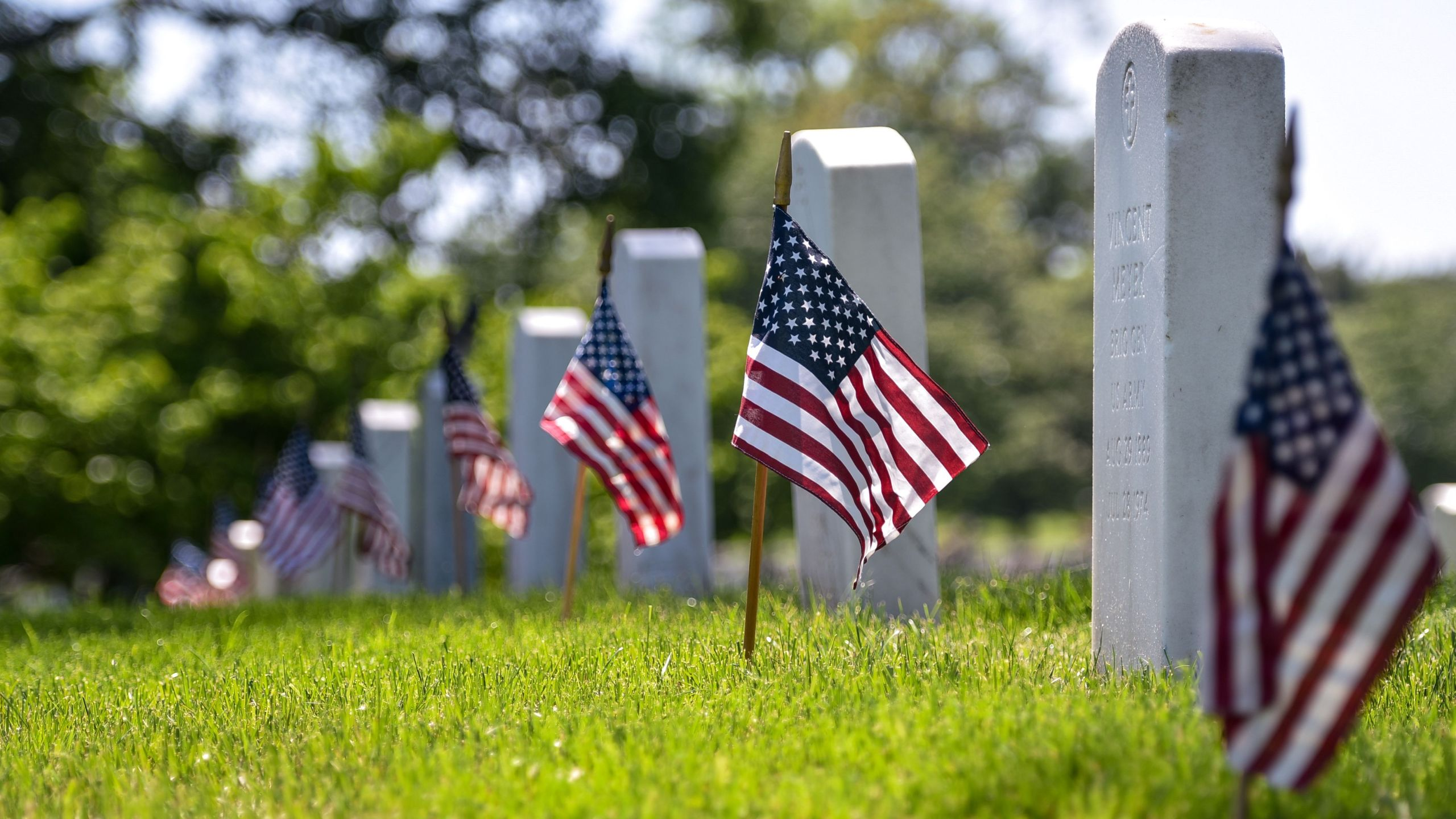 US flags are placed at graves by members of the Old Guard are seen at Arlington National Cemetery on May 24, 2018 ahead of Memorial Day in Arlington, Virginia. (Photo by Mandel NGAN / AFP) (Photo credit should read MANDEL NGAN/AFP/Getty Images)