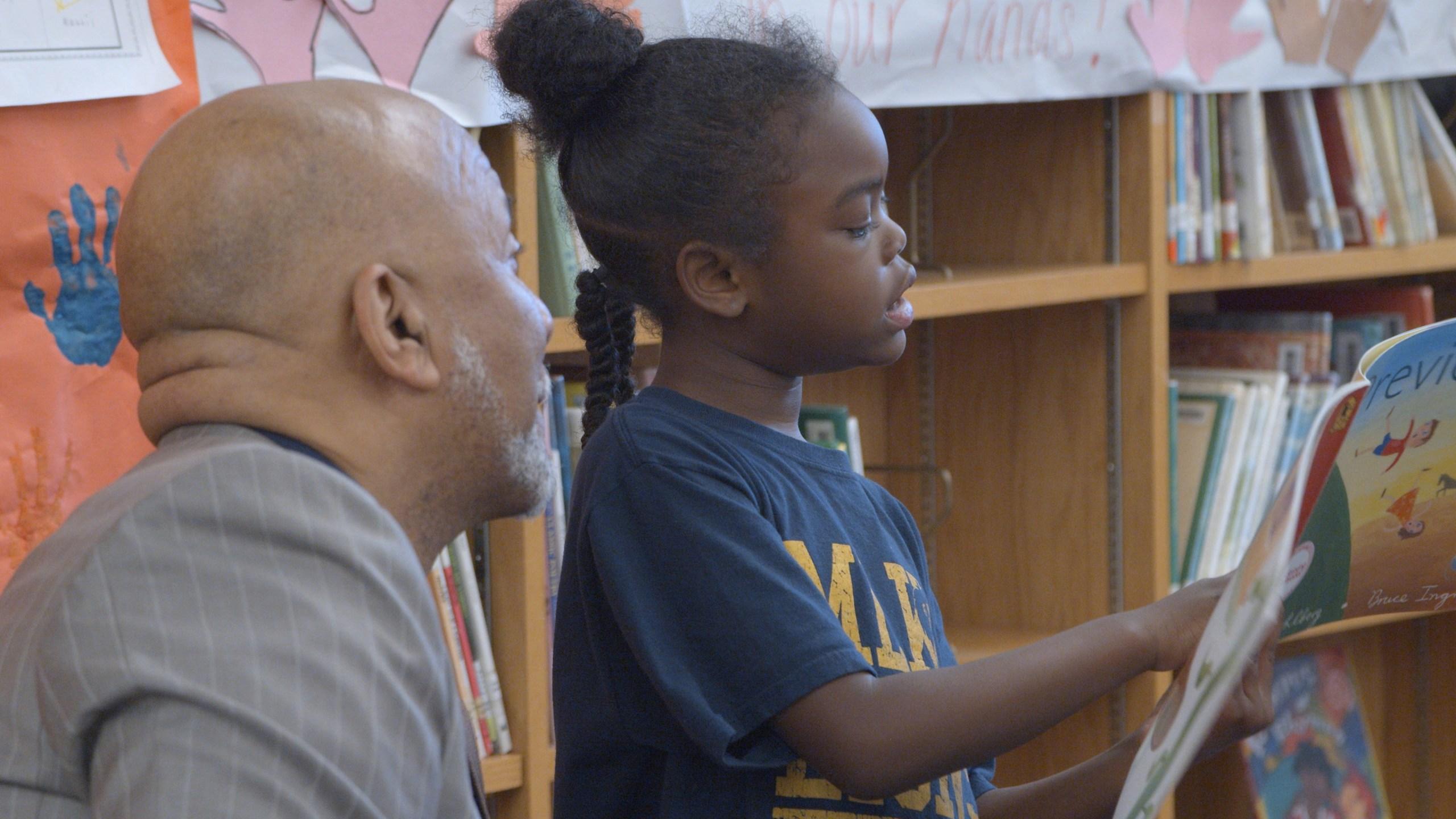 Thurman White, Jr. and student reading aloud at Raising a Reader