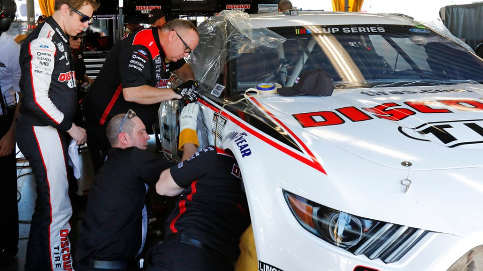 Image of Brad Kaselowski working on a car with