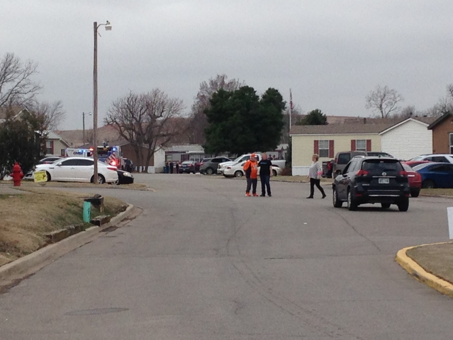 This is a picture of the scene of a reported shooting in southwest Oklahoma City. The image is people standing in a road with homes behind them.