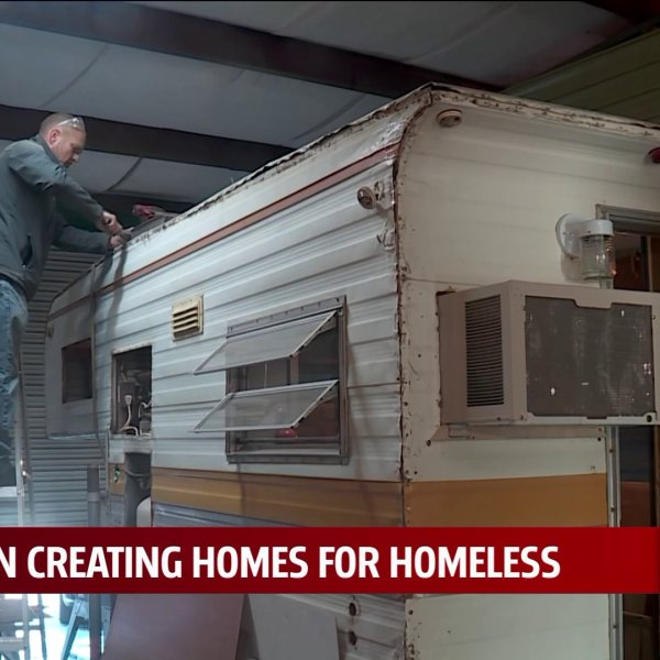 Ryan Laughlin fixes trailer for a home for the homeless
