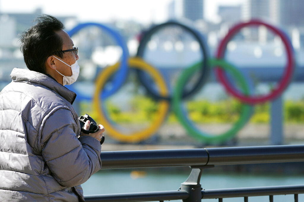 A visitor wearing a face mask stands near the Olympic rings at Tokyo's Odaiba district Tuesday, March 24, 2020. The Tokyo Olympics are probably going to happen, but almost surely in 2021 rather than in four months as planned. (AP Photo/Eugene Hos