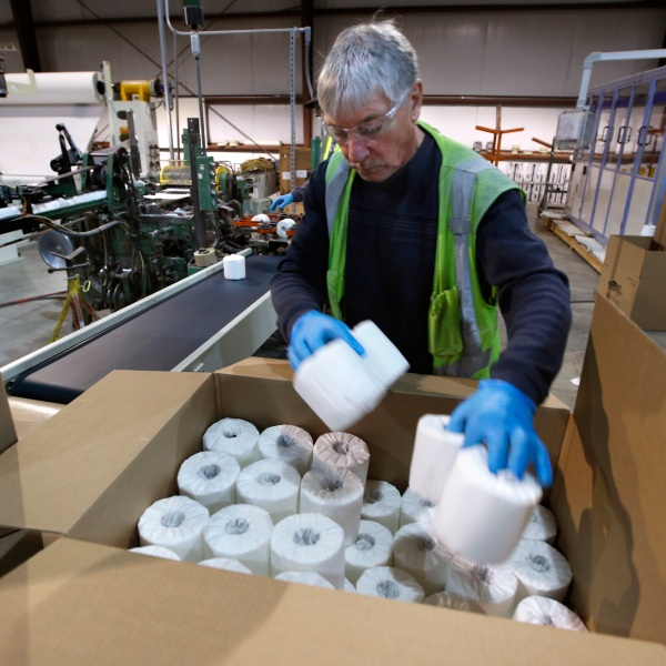Scott Mitchell fills a box with toilet paper at the Tissue Plus factory