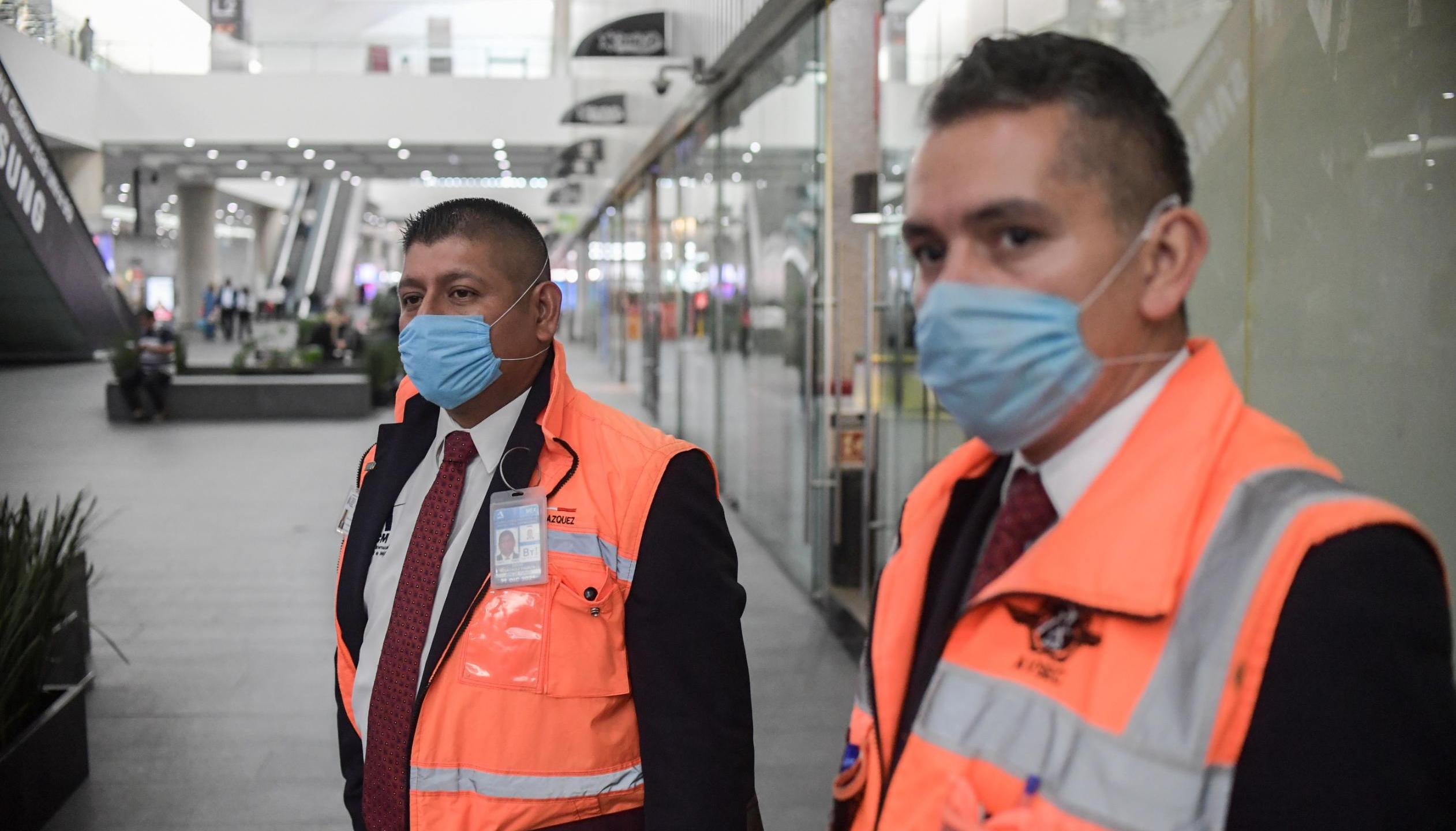 Employees wear protective masks as a preventive measure against the spread of coronavirus