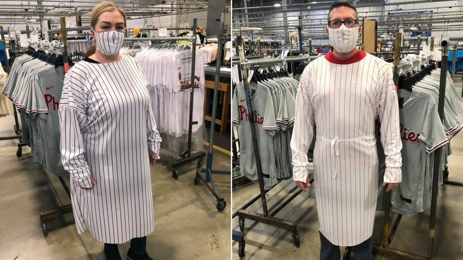 Two people model an example of a hospital gown and mask made from baseball jersey fabric.