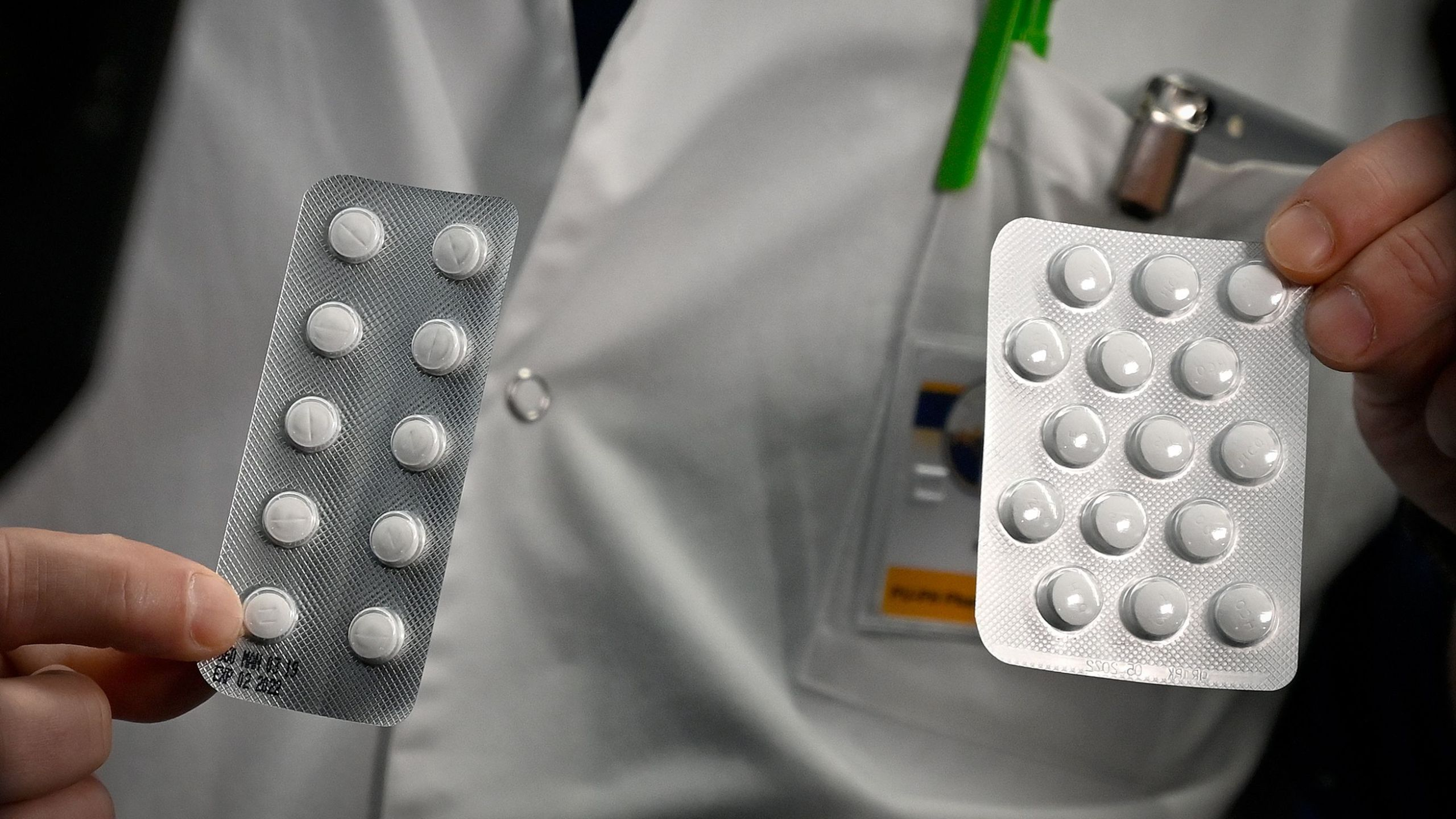 Doctor holds two packs of chloroquine pills