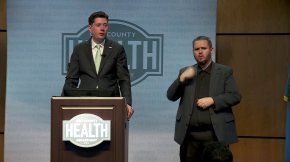 OKC Mayor David Holt talking at podium with sign language interpreter by his side