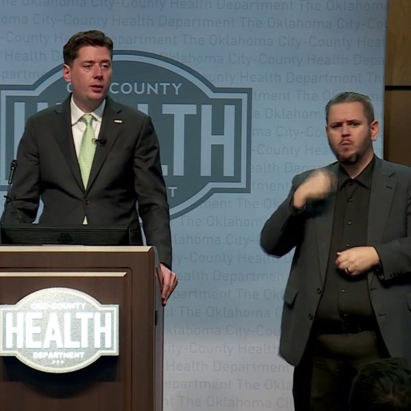 OKC Mayor David Holt talking at podium with sign language interpreter by his side