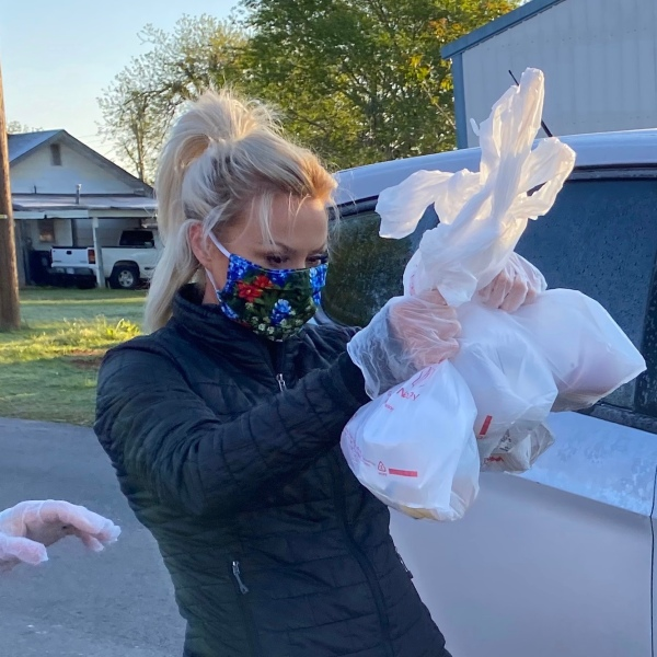 Joleen Chaney wearing mask and gloves to hand out meals to Rush Springs students