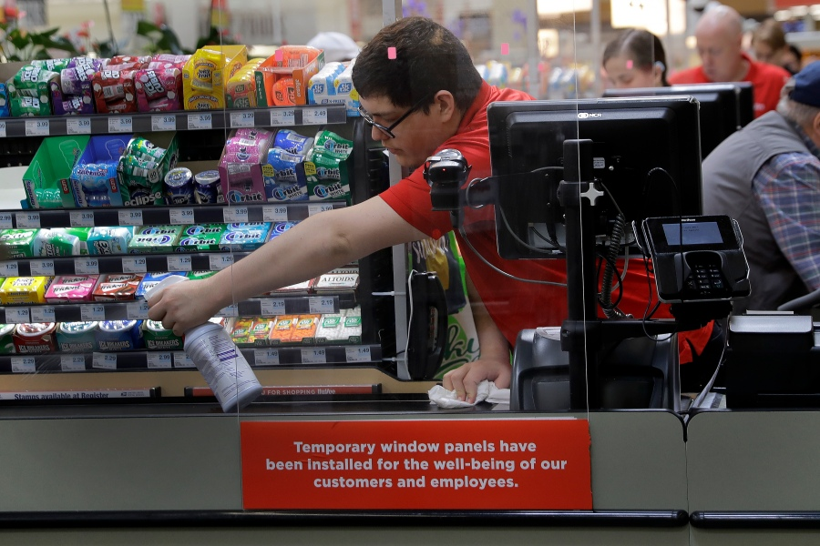 Garrett Ward sprays disinfectant on a conveyor belt between checking out shoppers behind a plexiglass panel at a Hy-Vee grocery store in Overland Park, Kan. From South Africa to Italy to the U.S., grocery workers — many in low-wage jobs — are manning the front lines amid worldwide lockdowns, their work deemed essential to keep food and critical goods flowing. (AP Photo/Charlie Riedel, File)