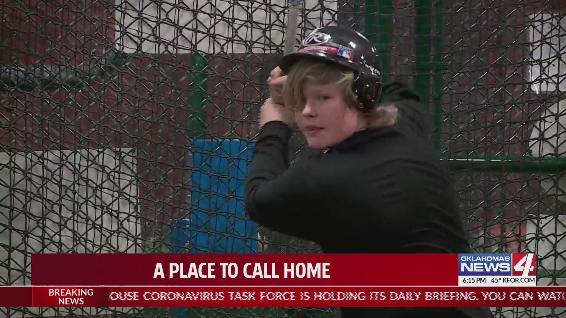 teen boy takes batting stance in batter's cage