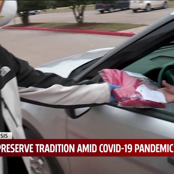 person wearing ppe hands off cap and gown to student in car