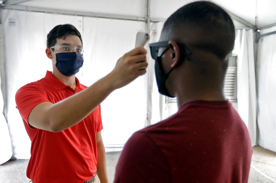 Matt Comstock. left, wearing a protective face-mask, takes the temperature of a guest at Busch Gardens Tampa Bay, Wednesday, June 10, 2020, in Tampa, Fla. Busch Gardens Tampa Bay is reopening on Thursday with some restrictions. The park closed on March 16, to help stopping the spread of the coronavirus. (AP Photo/Chris O'Meara)