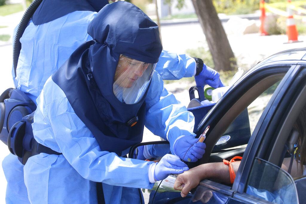 Salt Lake County Health Department's public health nurse Lee Cherie Booth performs a coronavirus anti-body test outside the Salt Lake County Health Department on Thursday in Salt Lake City. (AP Photo/Rick Bowmer)