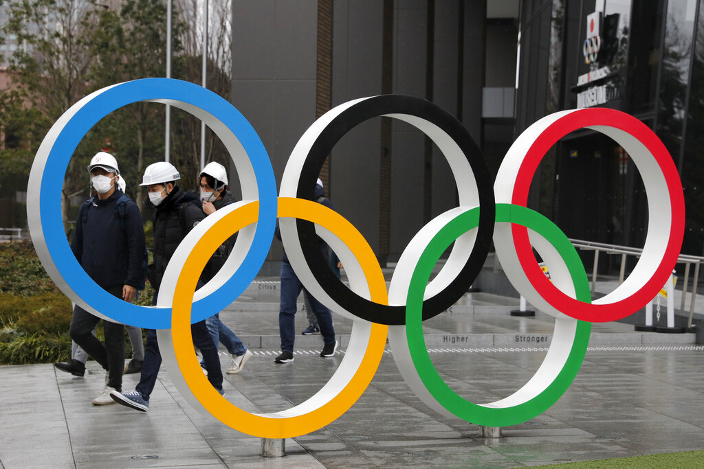 FILE - In this March 4, 2020, file photo, people wearing masks walk past the Olympic rings near the New National Stadium in Tokyo. Local Japanese sponsors have chipped in a record $3.3 billion to organize the postponed Tokyo Olympics. That's almost 60% of the income for the privately funded operating budget. With the games delayed for a year, sponsors will be asked to sign up again. (AP Photo/Jae C. Hong, File)