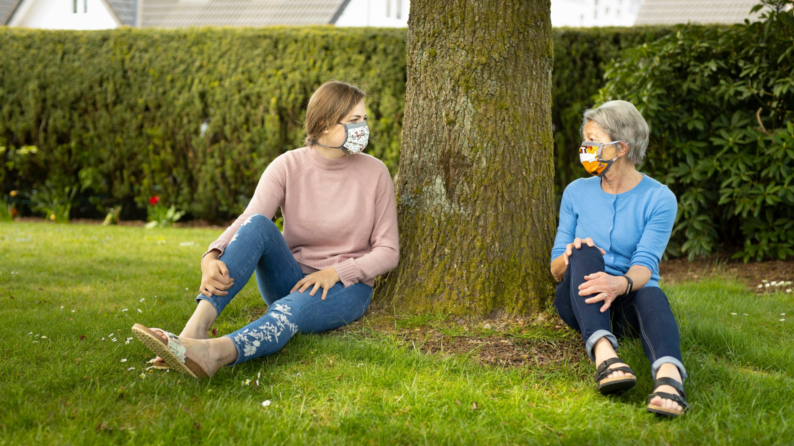 Two women sit under tree wearing masks