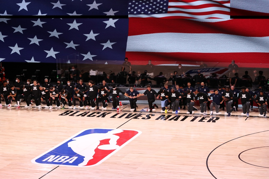 picture of NBA players kneeling with Black Lives Matter written on the floor