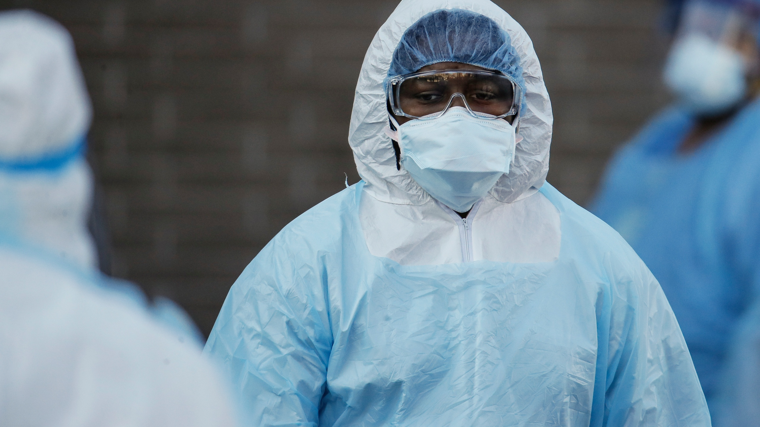 A medical worker wearing personal protective equipment pauses after wheeling a body to a refrigerated trailer serving as a makeshift morgue at Wyckoff Heights Medical Center, Monday, April 6, 2020, in the Brooklyn borough of New York. The new coronavirus causes mild or moderate symptoms for most people, but for some, especially older adults and people with existing health problems, it can cause more severe illness or death. (AP Photo/John Minchillo)