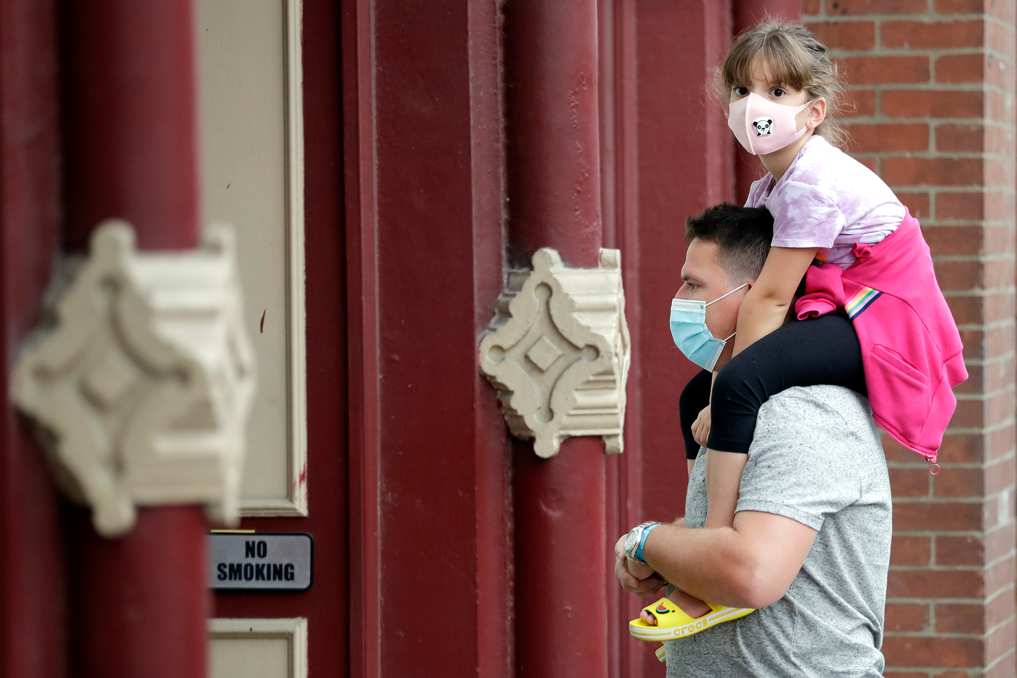 A man and a girl wear masks as they stop to hear a band outside a music venue Monday, June 29, 2020, in Nashville, Tenn. The Nashville Health Department has put in place a mask mandate beginning Monday to help battle the spread of the coronavirus. (AP Photo/Mark Humphrey)