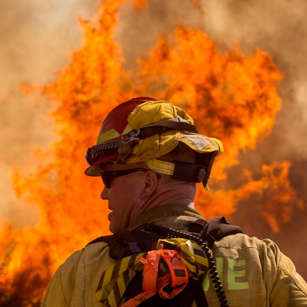 firefighter standing in front of large wildfire