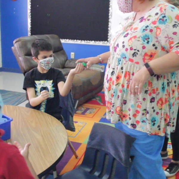 student gets hand sanitizer in classroom