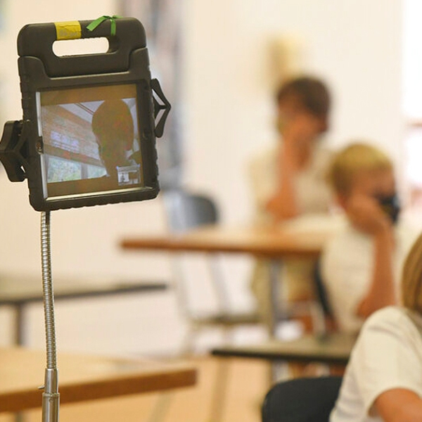 A student virtually attends class using a tablet on the first day of the 2020-2021 school year at Brunswick's Lower School in Greenwich, Conn., on Tuesday. Schools across the country are opening in a variety of ways during the coronavirus pandemic, including all in-person learning, all virtual learning, and a hybrid model mixed virtual and in-person learning. (Tyler Sizemore/Hearst Connecticut Media via AP)