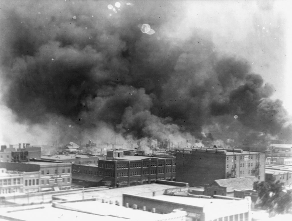 """In this 1921 image provided by the Library of Congress, smoke billows over Tulsa, Okla. For decades, when it was discussed at all, the killing of hundreds of people in a prosperous black business district in 1921 was referred to as the Tulsa race riot. Under new standards developed by teachers for approaching the topic, students are encouraged to consider the differences between labeling it a """"massacre"""" instead of a """"riot,"""" as it is still commemorated in state laws. (Alvin C. Krupnick Co./Library of Congress via AP)"""