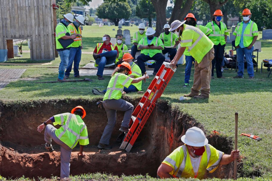In this July 14, 2020, file photo, workers climb out of the excavation site as work continues on a potential unmarked mass grave from the 1921 Tulsa Race Massacre, at Oaklawn Cemetery in Tulsa, Okla. (AP Photo/Sue Ogrocki File)