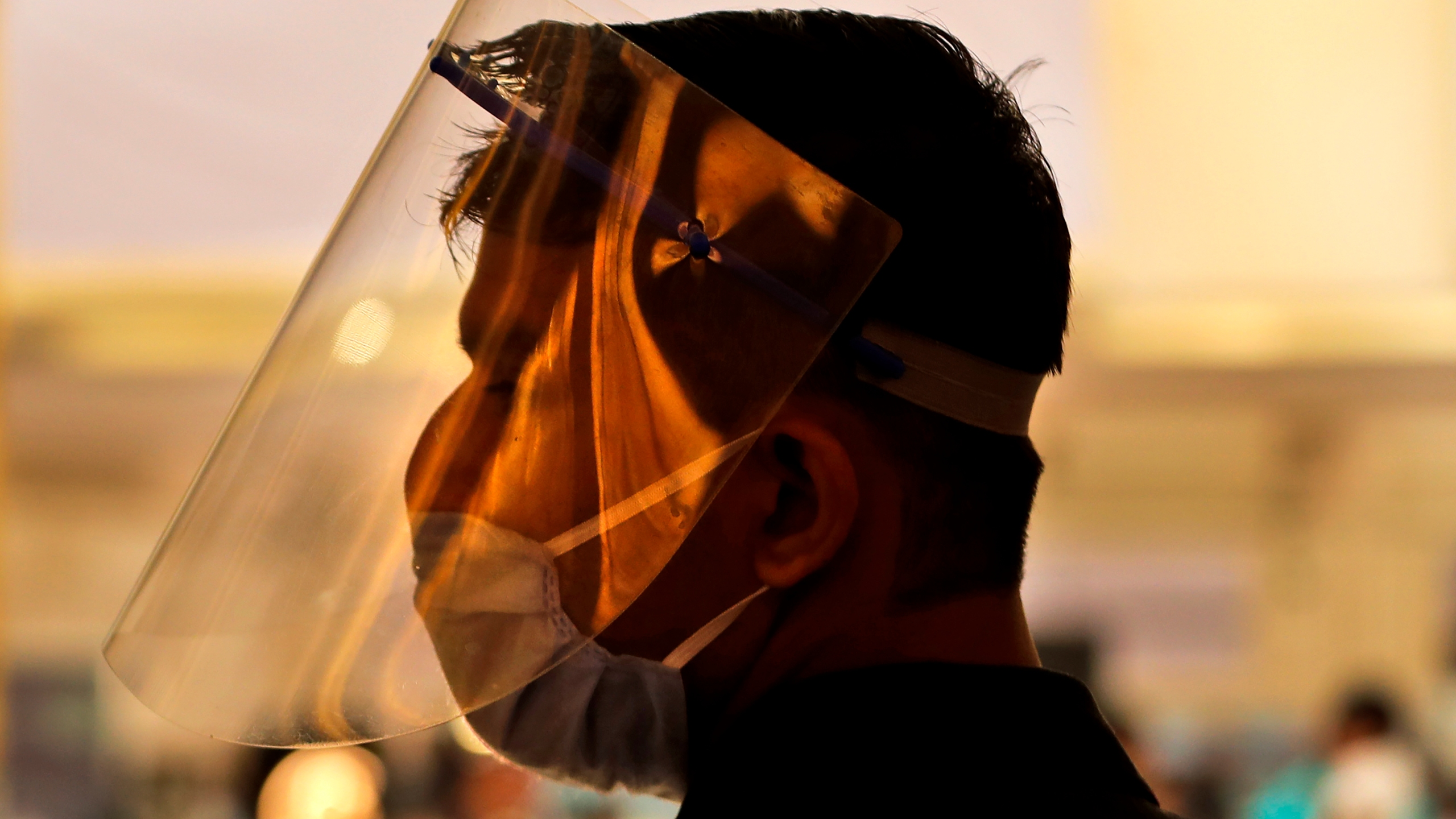 An employee of the PVR cinemas with a face shield and a mask stands at the entrance to welcome people in New Delhi, India, Thursday, Oct. 15, 2020. Seven months after screens went dark, cinemas reopened Thursday in much of India with mostly old titles on the marquee — a sign of the country's efforts to return to normal as the pace of coronavirus infections slows but also of the roadblocks that remain. (AP Photo/Manish Swarup)