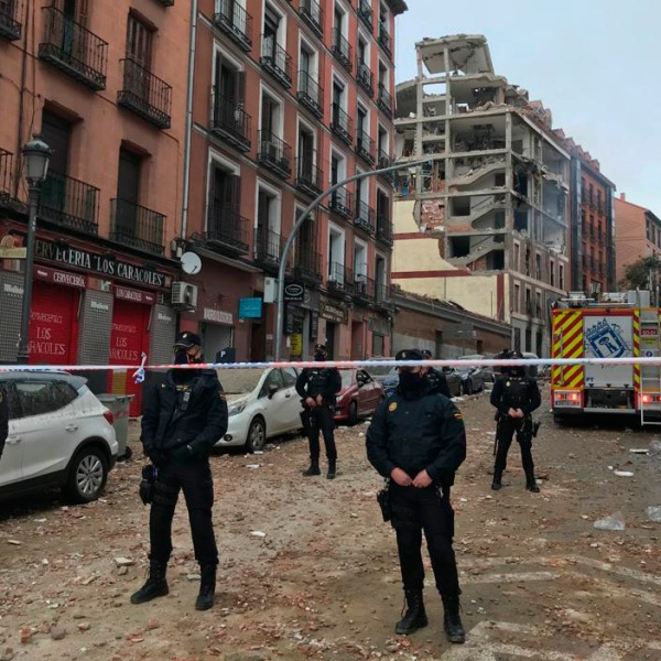Police officers cordon off Toledo Street following an explosion in downtown Madrid, Spain, Wednesday, Jan. 20, 2021. A loud explosion of unknown origin has partially destroyed a six-floor-tall building flanked by a school and a nursing home in the center of Spain's capital, Madrid. (AP Photo/Bernat Armangue)
