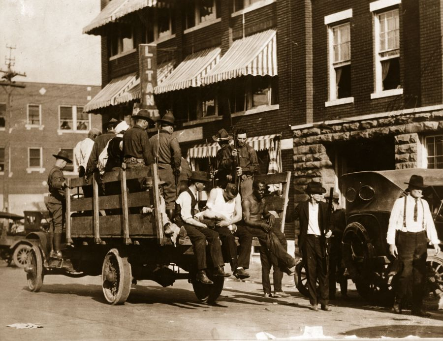 """3rd June 1921: injured and wounded men are being taken to hospital by National guardsmen after racially motivated riots, also known as the """"Tulsa Race Massacre"""", during which a mobs of white residents attacked black residents and businesses of the Greenwood District in Tulsa, Oklahoma, US. (Photo by Hulton Archive/Getty Images)"""