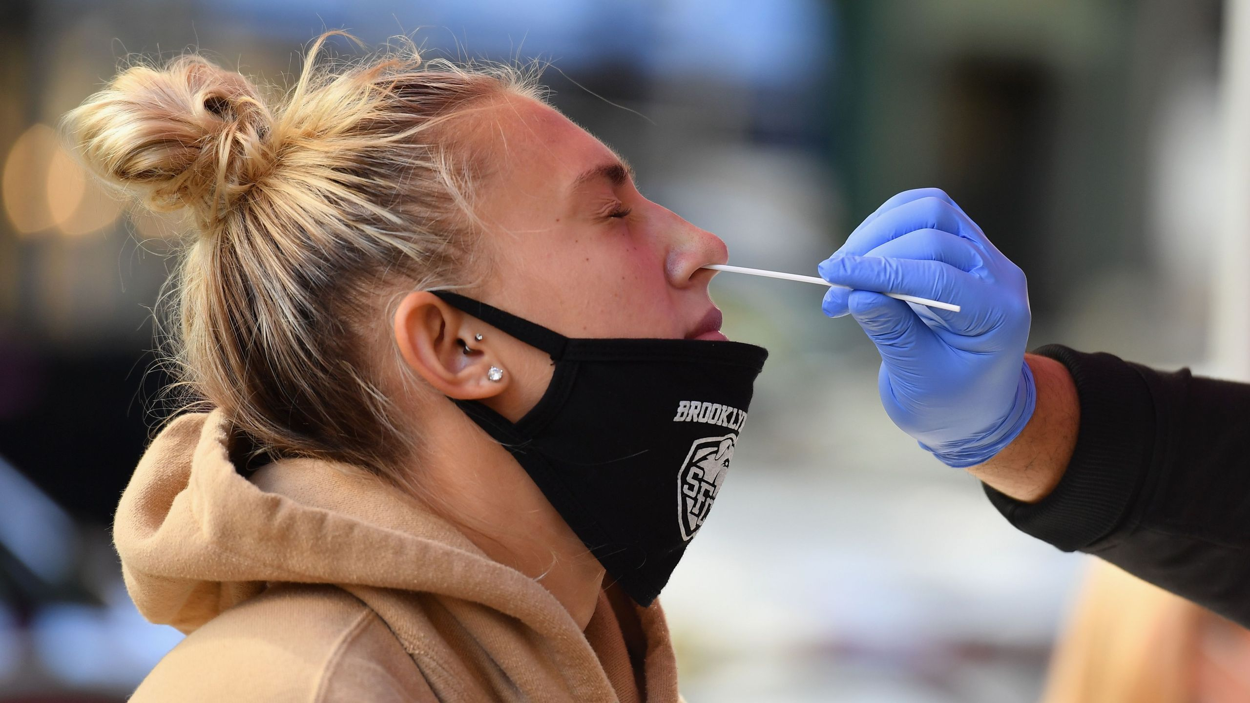 A medical worker takes a nasal swab sample from a student to test for COVID-19 at the Brooklyn Health Medical Alliance urgent care pop up testing site in New York City. New York's governor (Photo by ANGELA WEISS/AFP via Getty Images)