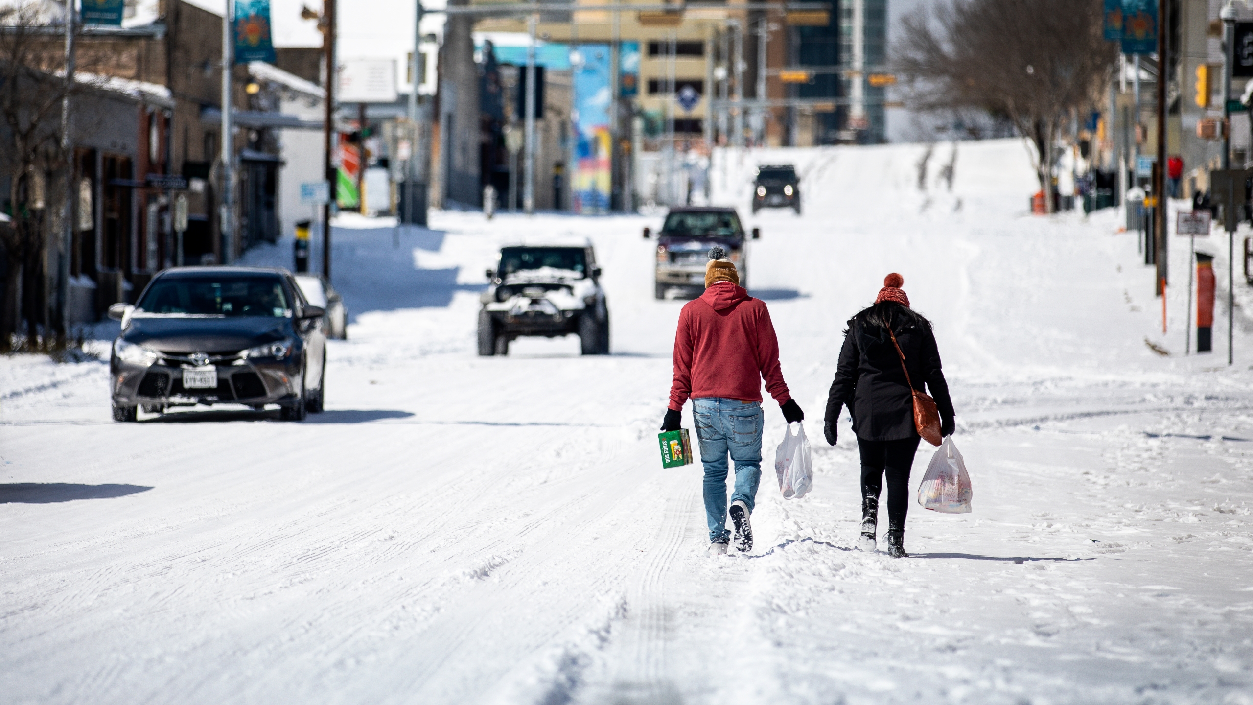 People carry groceries from a local gas station on February 15, 2021 in Austin, Texas. Winter storm Uri has brought historic cold weather to Texas, causing traffic delays and power outages, and storms have swept across 26 states with a mix of freezing temperatures and precipitation. (Photo by Montinique Monroe/Getty Images)