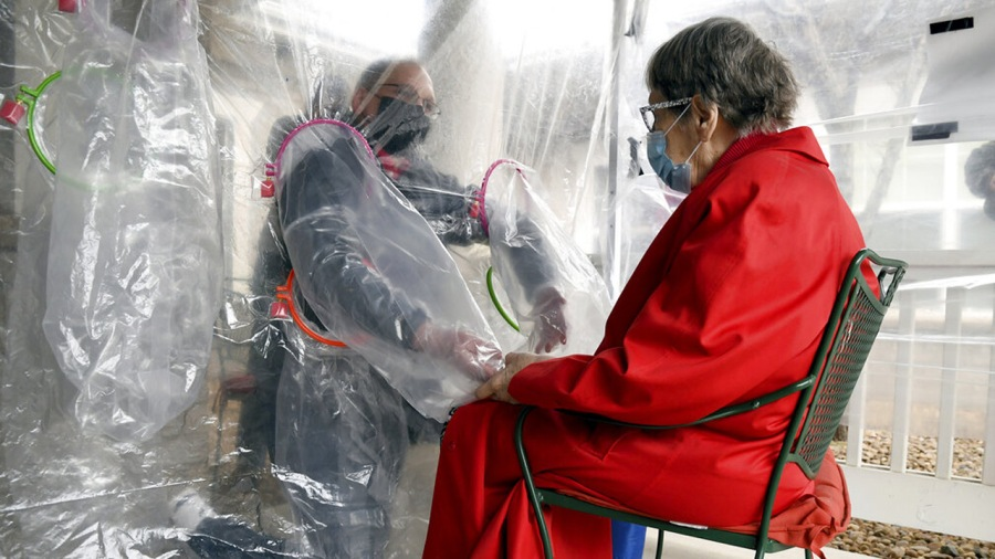 """Gregg MacDonald holds hands with his 84-year-old mother, Chloe MacDonald, at a """"hug tent"""" set up outside the Juniper Village assisted living center in Louisville, Colo., Wednesday, Feb. 3, 2021. The tent includes a construction-grade plastic barrier with built-in plastic sleeves to prevent the spread of the coronavirus. (AP Photo/Thomas Peipert)"""