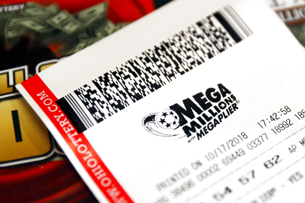 In this Oct. 17, 2018, file photo a Mega Millions lottery ticket rests on the shop counter at the Street Corner Market in Cincinnati. (AP Photo/John Minchillo, File)