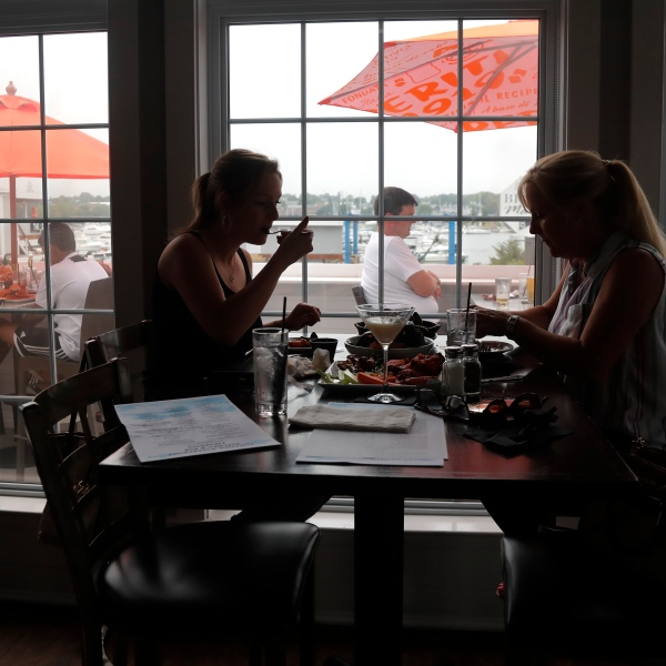 In this June 22, 2020, file photo two women eat lunch indoors at Portside Restaurant in Salisbury, Mass., after COVID-19 state guidelines allowed for indoor dining. (AP Photo/Elise Amendola, File)