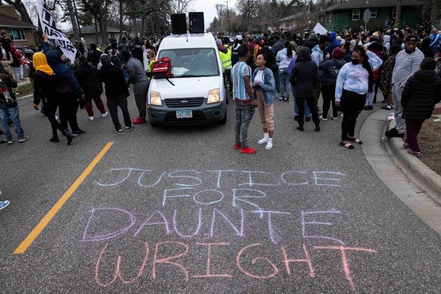 People gather in protest, Sunday, April 11, 2021, in Brooklyn Center, Minn. The family of Daunte Wright, 20, told a crowd that he was shot by police Sunday before getting back into his car and driving away, then crashing the vehicle several blocks away. The family said Wright was later pronounced dead. (AP Photo/Christian Monter