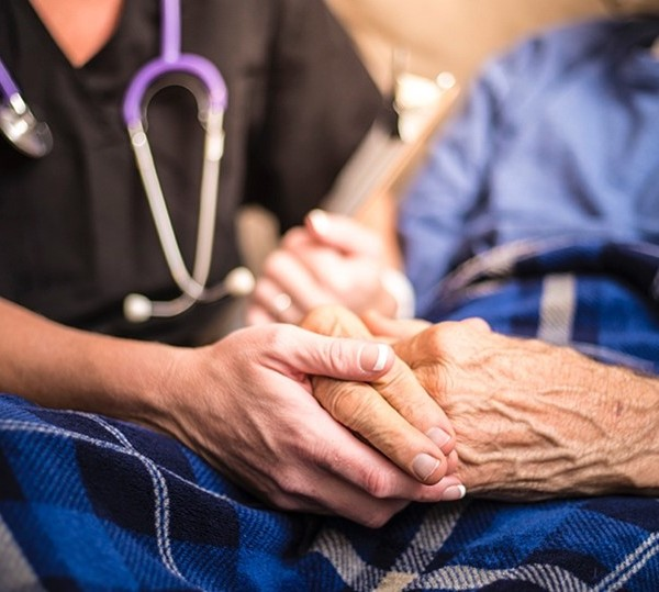 Caregiver holds hands with elderly patient