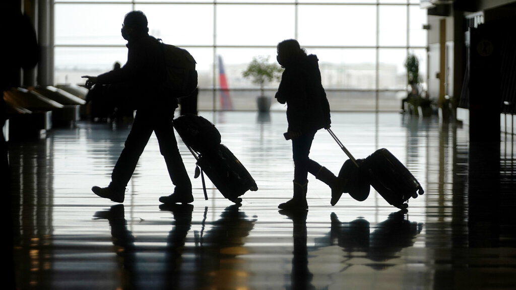 Travelers walk through the Salt Lake City International Airport, in Salt Lake City. The number of people flying in the United States has eclipsed the year-ago level for the first time in the pandemic period, although travel remains deeply depressed from 2019. The Transportation Security Administration said 1.34 million people passed through U.S. airport checkpoints on Sunday, March 14 topping the 1.26 million people that TSA screened on the comparable Sunday a year ago. (AP Photo/Rick Bowmer, File)