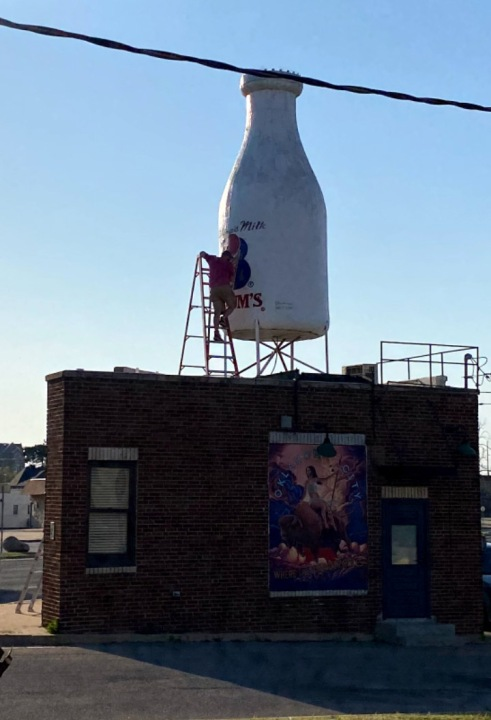 Local muralist Christ Presley works on the iconic Braum's milk bottle ad