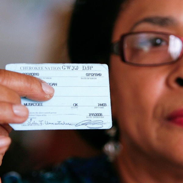 """In this Oct. 6, 2011 photo, Rena Logan, a member of a Cherokee Freedmen family, shows her identification card as a member of the Cherokee tribe at her home in Muskogee, Okla. Thousands of people whose ancestors were enslaved by the Cherokee Indians in the 1800s are fighting to keep their status as members of the tribe. Loss of citizenship could also mean losing valuable tribal benefits such as medical care, housing assistance and grocery stipends. Logan, a retired cook who keeps her ancestors' Freedmen Roll number of 3918 close to her heart every day, gets treatment at tribal clinics for her arthritis, hypertension, osteoarthritis and a dislocated back disc. """"We are black, and we were slaves, and they want to keep us that way,"""" Logan said. """"It really hurts the heart. What did we do to be discriminated against?"""" (AP Photo/Dave Crenshaw)"""