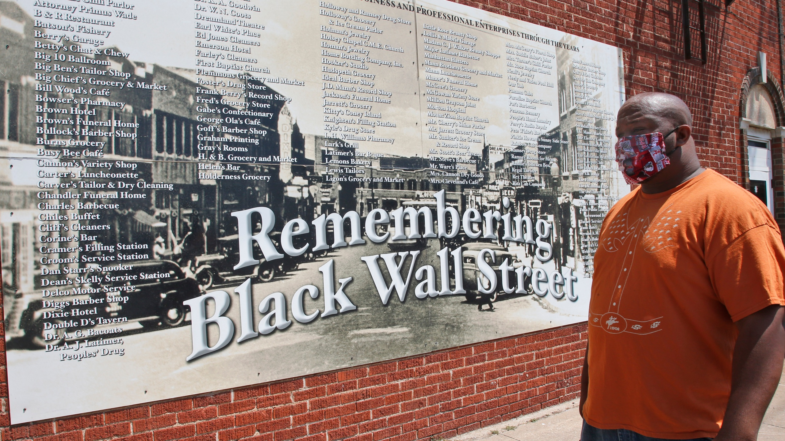 FILE - In this June 15, 2020 file photo, Freeman Culver stands in front of a mural listing the names of businesses destroyed during the 1921 Tulsa Race Massacre in Tulsa, Okla. Attorneys for victims and their descendants affected by the 1921 massacre filed a lawsuit in state court on Tuesday, Sept. 1, 2020, against the City of Tulsa and other defendants seeking reparations for the destruction of the city's once thriving Black district. (AP Photo/Sue Ogrocki File)