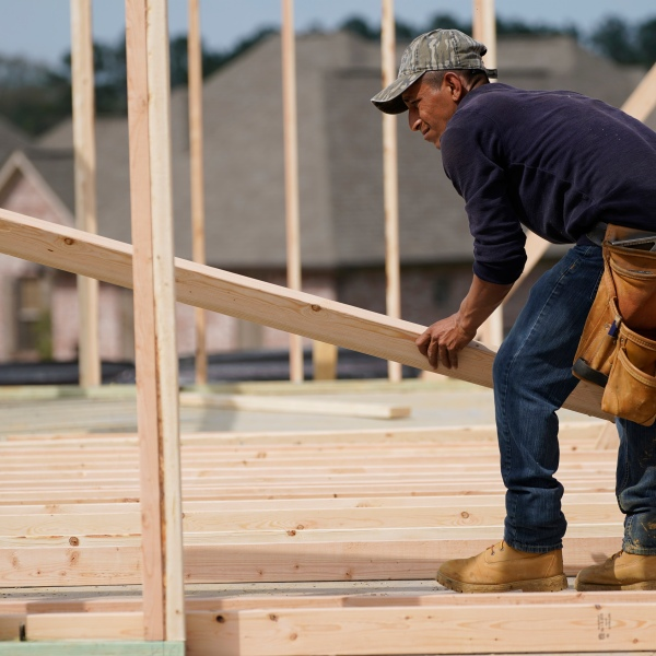 A carpenter aligns a beam for a wall frame at a new house site in Madison County, Miss., Tuesday, March 16, 2021. U.S. home construction fell by a bigger-than-expected amount in April but the drop came after housing had risen to the highest level in 15 years. The Commerce Department said Tuesday, May 18, that construction dropped 9.5% in April to a seasonally adjusted annual rate of 1.57 million units. % in April to an annual rate of 1.76 million units, a good sign that the April dip in construction will be temporary. (AP Photo/Rogelio V. Solis)