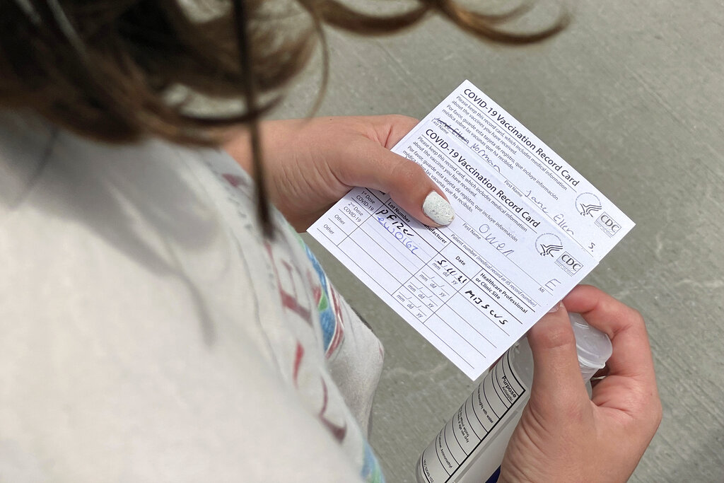 Jane Ellen Norman, 12, holds vaccination cards for her and her 14-year-old brother Owen