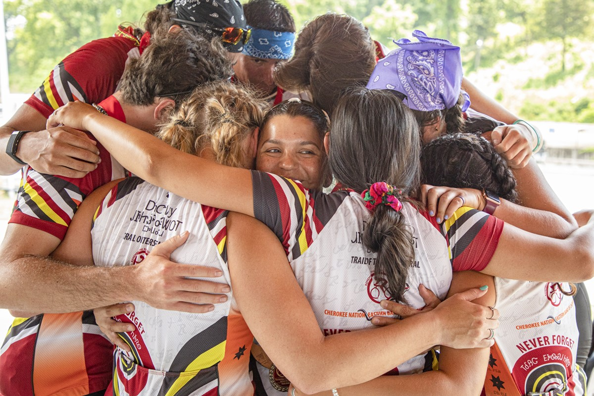 Nine Cherokee bicyclists who were part of the 2021 Remember the Removal Bike Ride embrace after finalizing their 950-mile journey on Friday with a homecoming ceremony in the capital city of the Cherokee Nation.