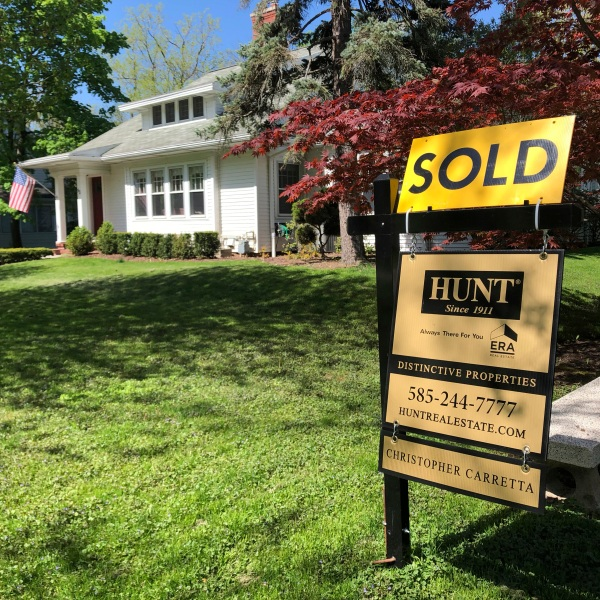 a sold sign sits in front of a house in Brighton, N.Y.