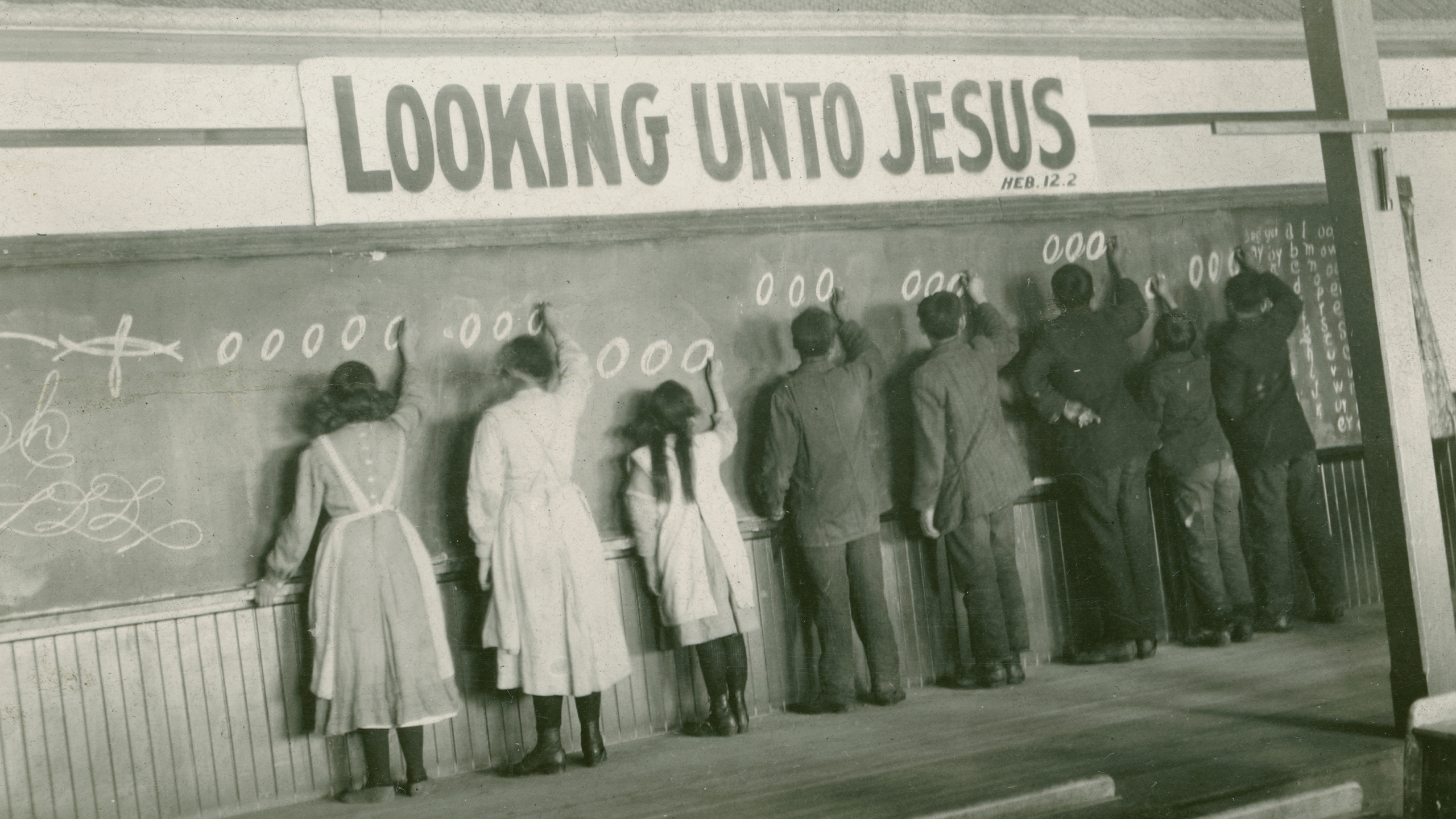 In this 1910s photo provided by the United Church of Canada Archives, students write on a chalkboard at the Red Deer Indian Industrial School in Alberta.