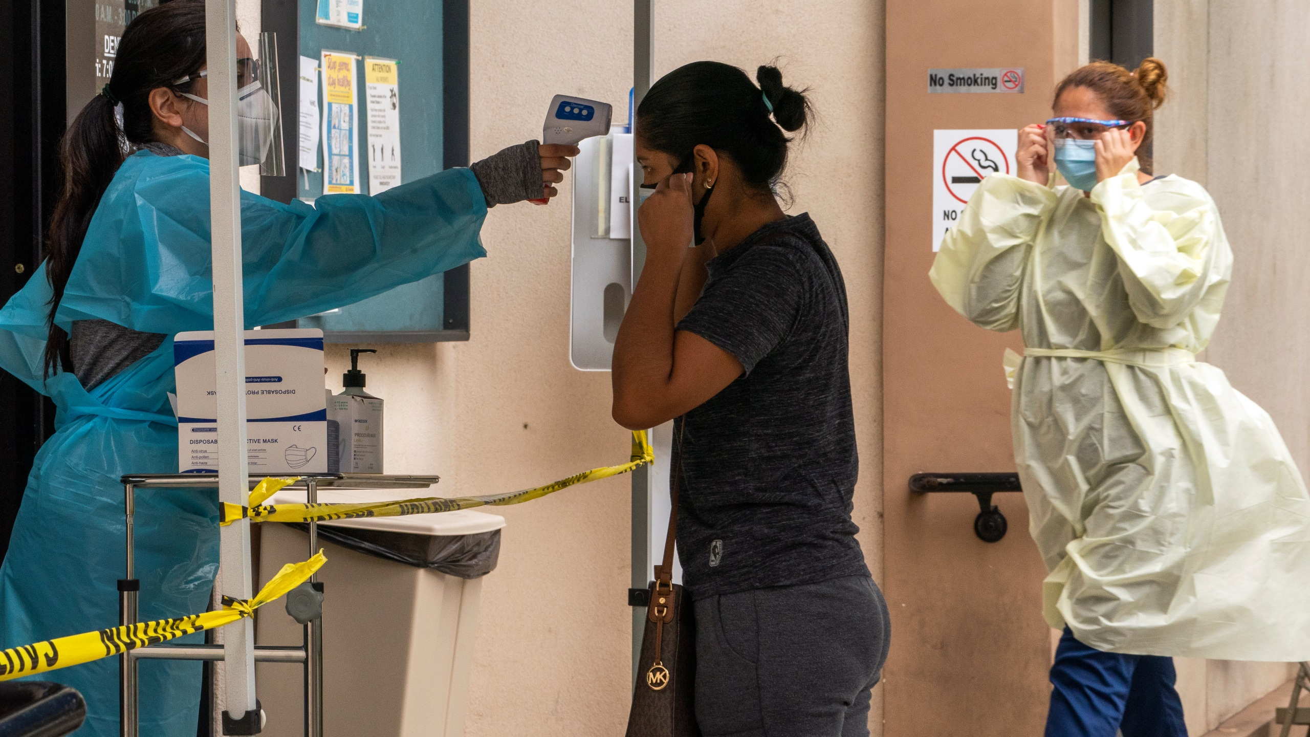 A patient has her body temperature screened after showing her COVID-19 vaccine card